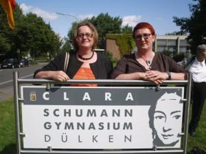 """Frau Büttner & Frau Jansen vor dem Schulschild - Die """"Macherinnen"""" in Sachen Logo"""